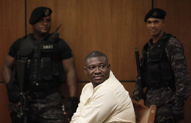 Haitian criminal Jolicoeur is escorted by Dominican policemen while he waits for the start of the tribunal regarding his extradition to France, at a courtroom in Santo Domingo